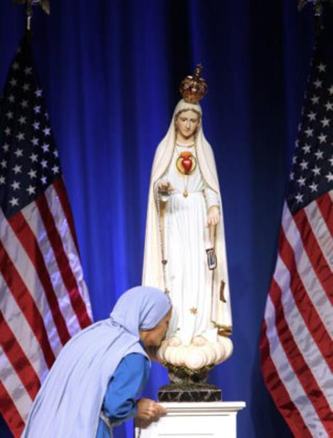 Iraqi-born Mother Olga of the Sacred Heart, founder of the Daughters of Mary of Nazareth, kisses a statue of Mary as she arrives to speak during the National Catholic Prayer Breakfast June 6 in Washington. (CNS photo/Bob Roller) See PRAYER-BREAKFAST June 6, 2017.